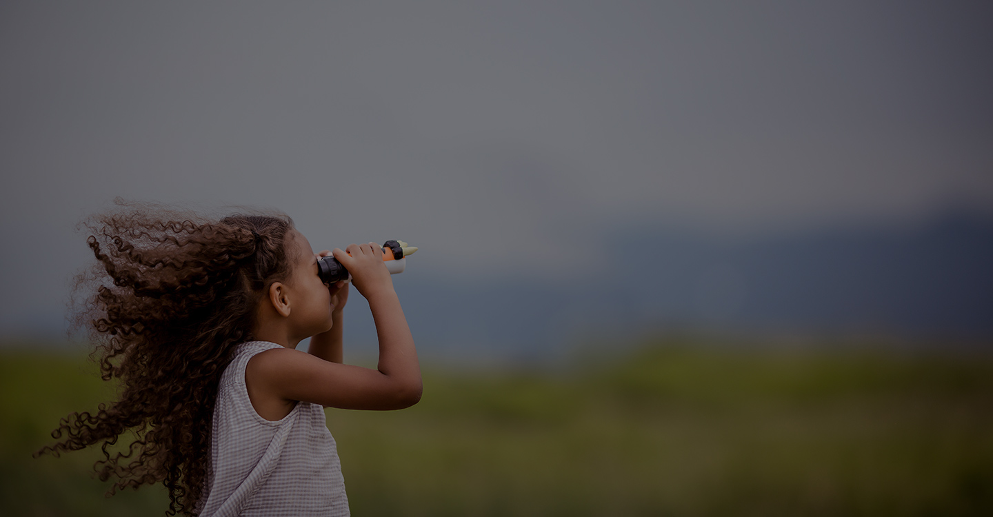 Young girl in a field looking through binoculars