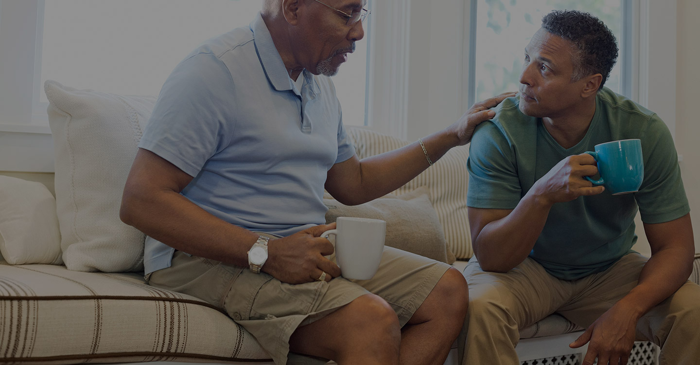 Father and son having coffee and talking about caregiver options for their family