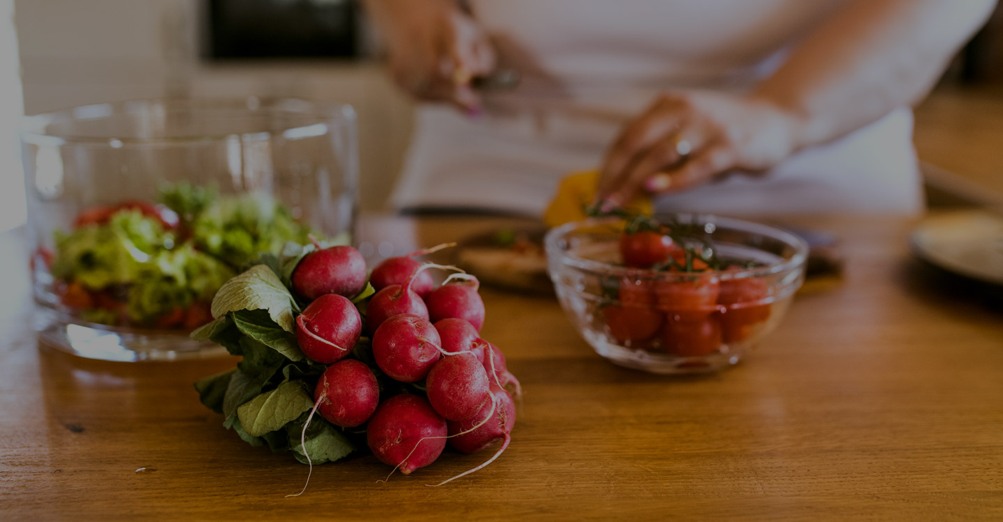 Radishes and a bowl strawberries sit on a counter while a woman prepares a healthy meal