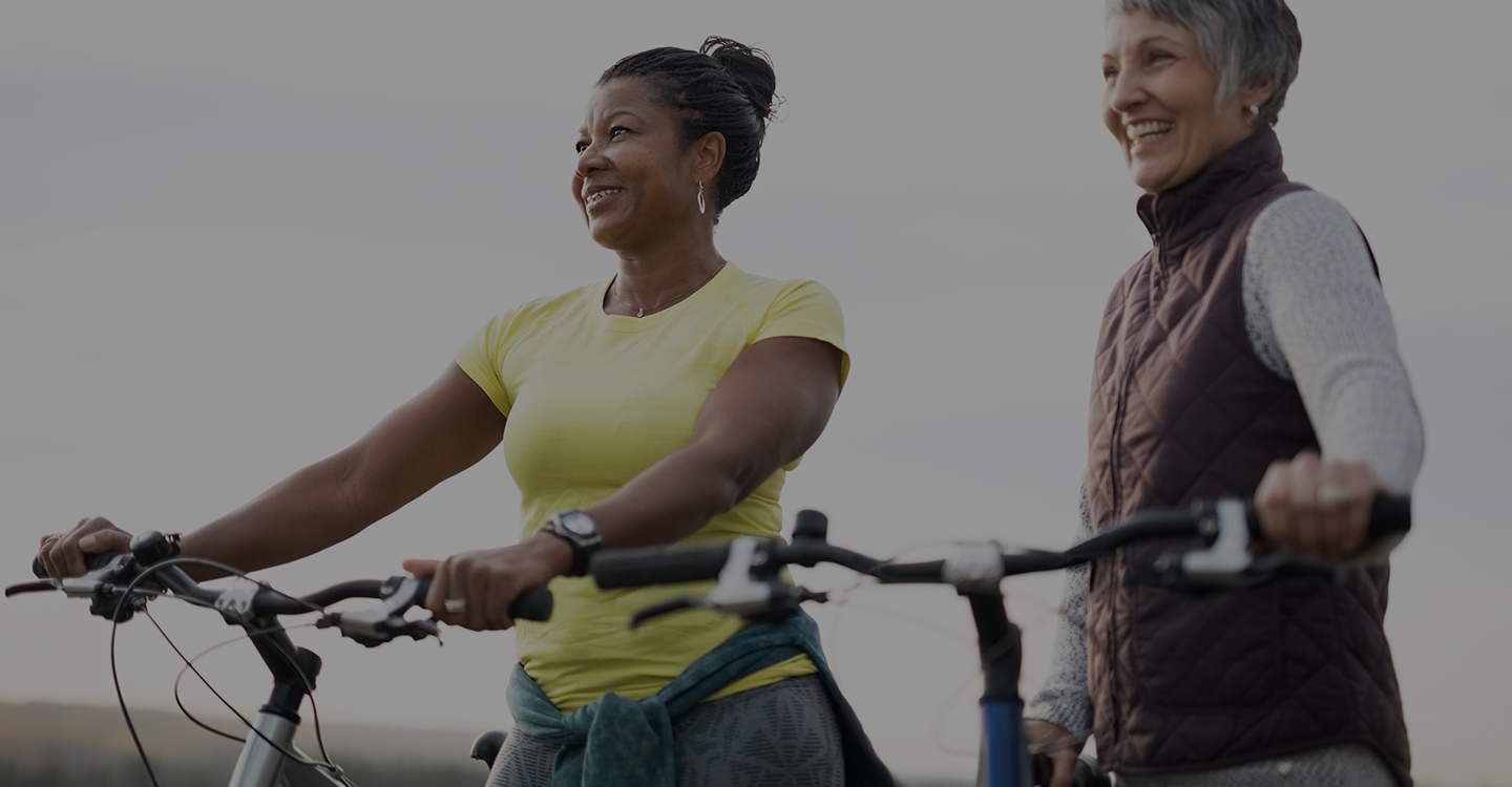 Two women enjoy biking outside as part of a healthy weight loss program
