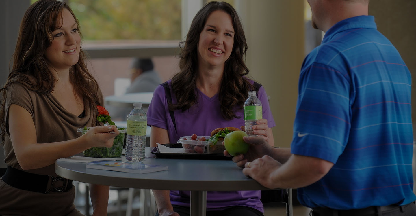 Three smiling employees enjoy a healthy lunch