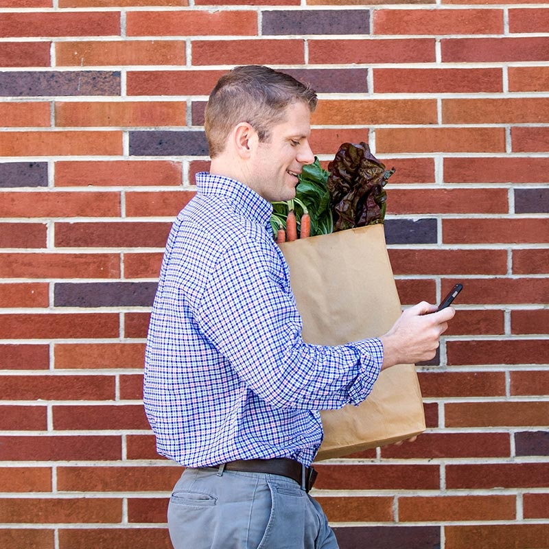 A man looks at his cell phone while carrying a grocery bag full of healthy food options