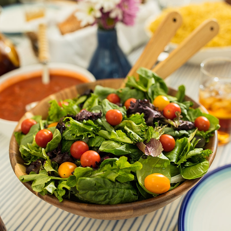 A nutrient dense bowl of salad sits on a table surrounded by low-sugar food options