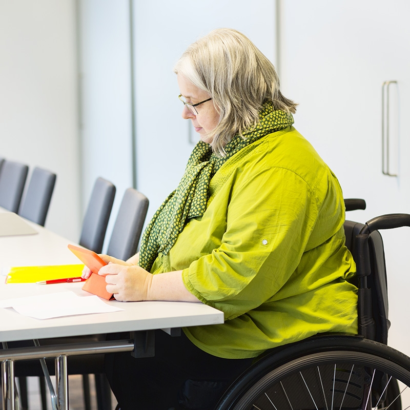 Woman in a wheelchair volunteering her time to help people register for health programs and classes