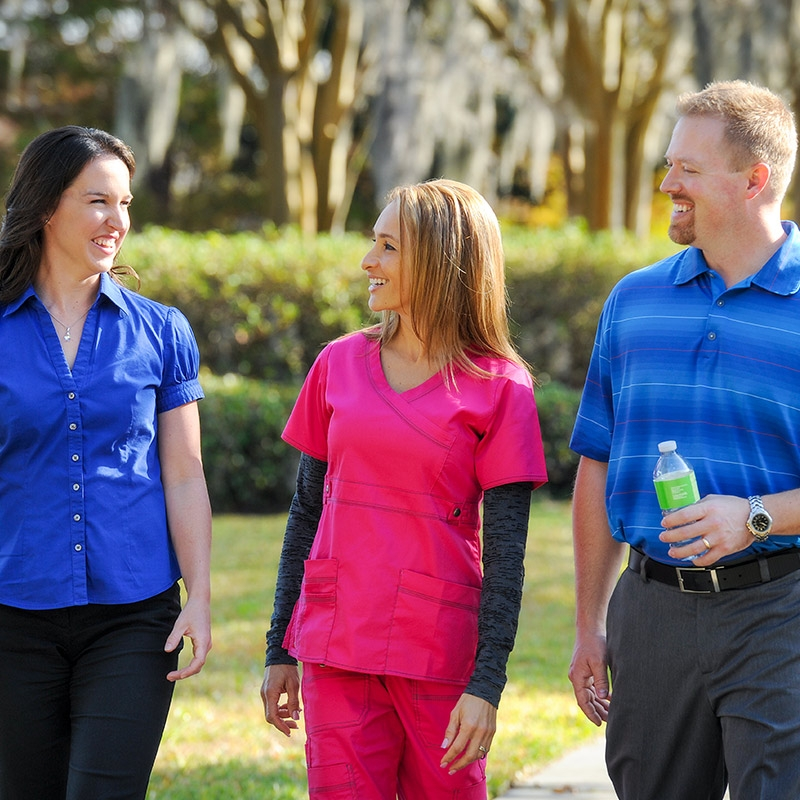 A diabetes care team member in pink medical scrubs chats with patients while walking outside