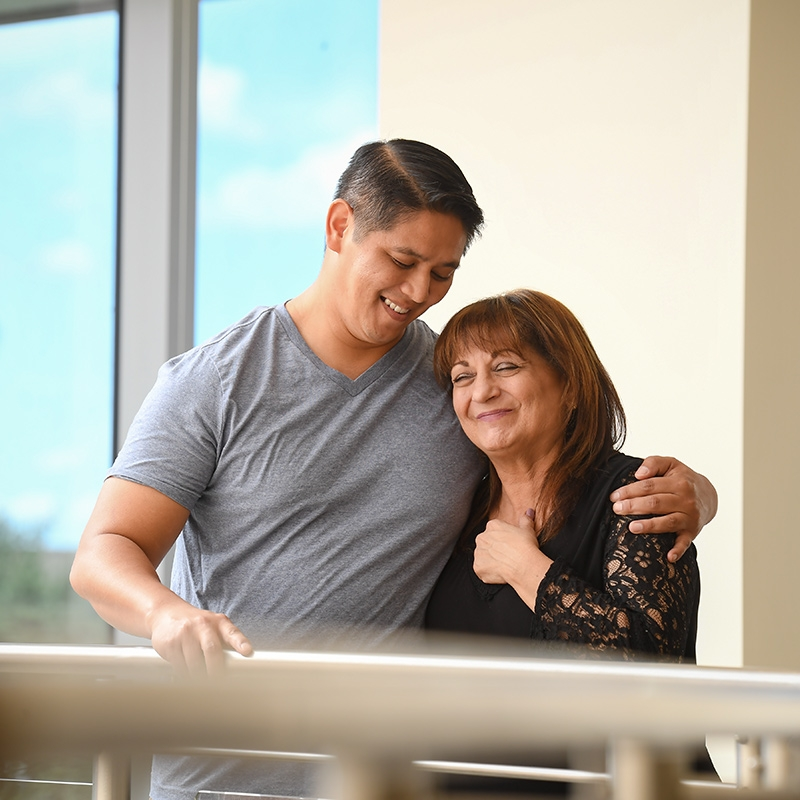 A man and woman embrace on a balcony after donating to a community wellness program